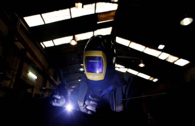 FILE PHOTO: Mitsos Dan, a worker from Albania, welds parts of agricultural machinery at a factory in Athens
