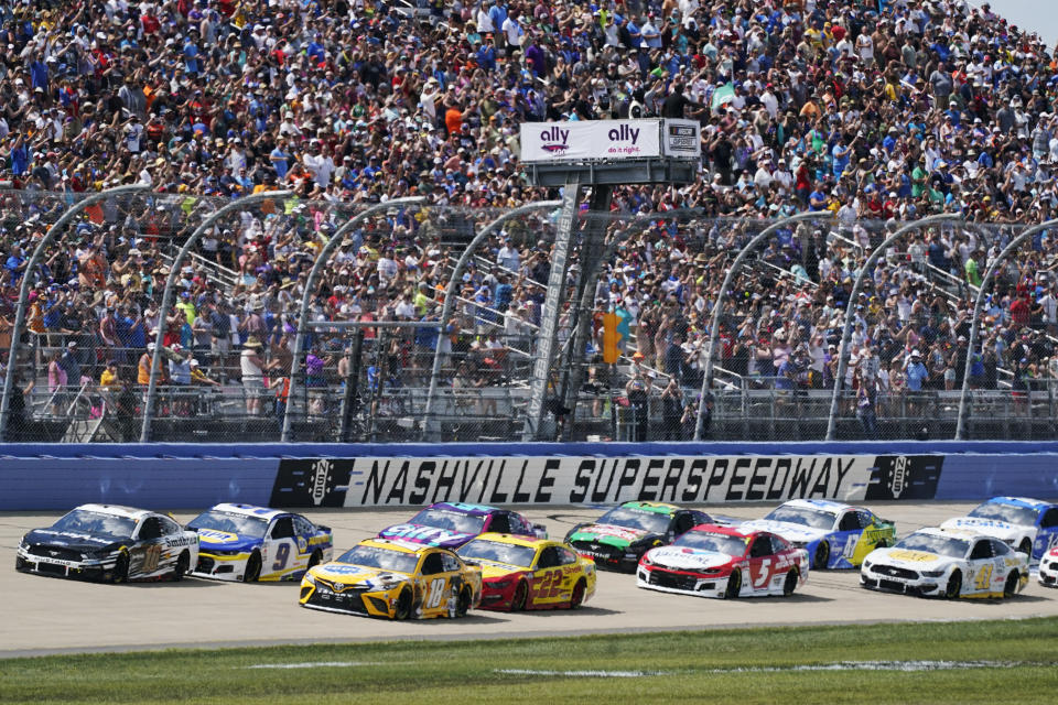 Aric Almirola (10) and Kyle Busch (18) lead the pack at the start of a NASCAR Cup Series auto race at Nashville Superspeedway Sunday, June 20, 2021, in Lebanon, Tenn. (AP Photo/Mark Humphrey)