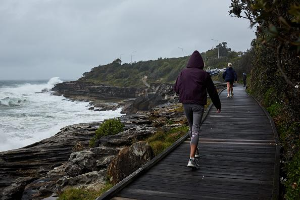 A woman walks in strong winds and rainy conditions at South Curl Curl beach in Sydney, Australia.