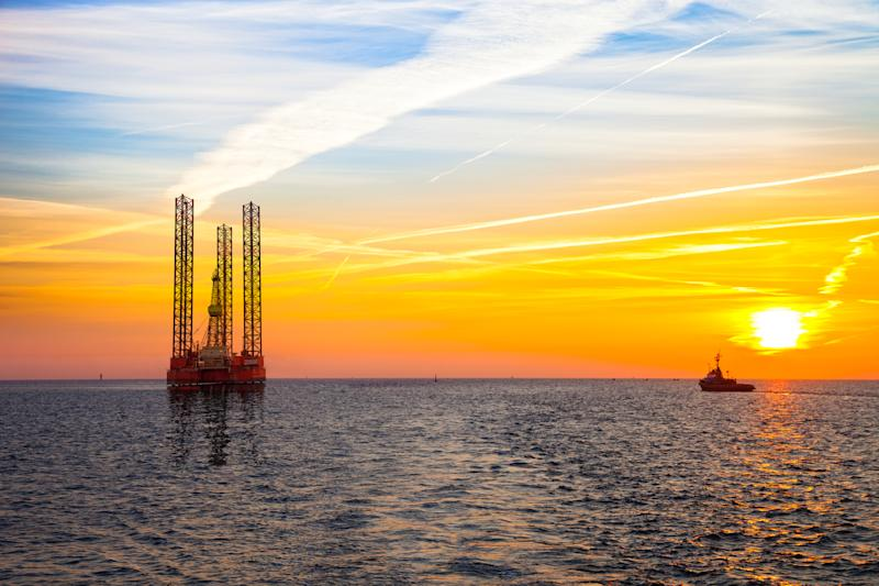 An offshore rig at sunset with a ship in the background.