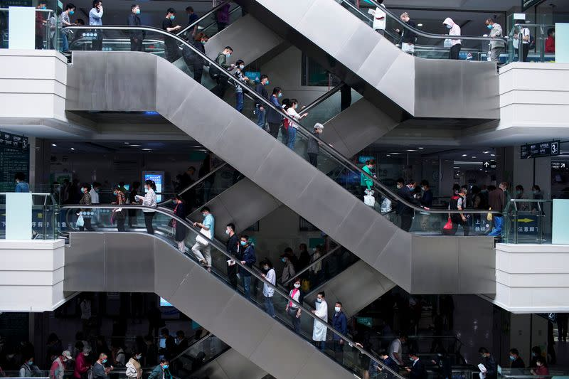 People wearing face masks stand on escalators at a hospital