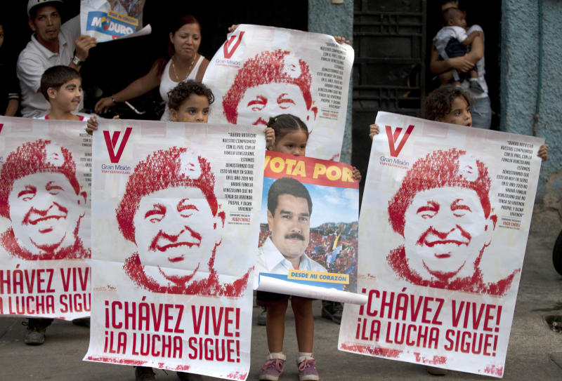 Children hold up posters of Venezuela's late President Hugo Chavez and one of ruling party candidate Nicolas Maduro as a campaign convoy drives along in Caracas, Venezuela, Wednesday, April 10, 2013. Maduro, the hand-picked successor of the late President Hugo Chavez, is running for president against opposition candidate Henrique Capriles. The presidential election is set for Sunday, April 14. (AP Photo/Ramon Espinosa)