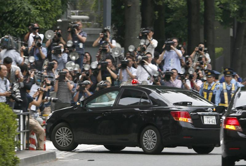 A police car believed to be carrying Katsuya Takahashi, a former Aum Shinrikyo cult member, pass by photographers and TV cameramen to enter Tokyo Metropolitan Police Department in Tokyo Friday, June 15, 2012. Police arrested Friday Takahashi, 54, the last fugitive suspected in the doomsday cult's deadly nerve gas attack on Tokyo subways 17 years ago. He was spotted at a comic book cafe in downtown Tokyo earlier in the day. (AP Photo/Kyodo News) JAPAN OUT, MANDATORY CREDIT, NO LICENSING IN CHINA, HONG KONG, JAPAN, SOUTH KOREA AND FRANCE