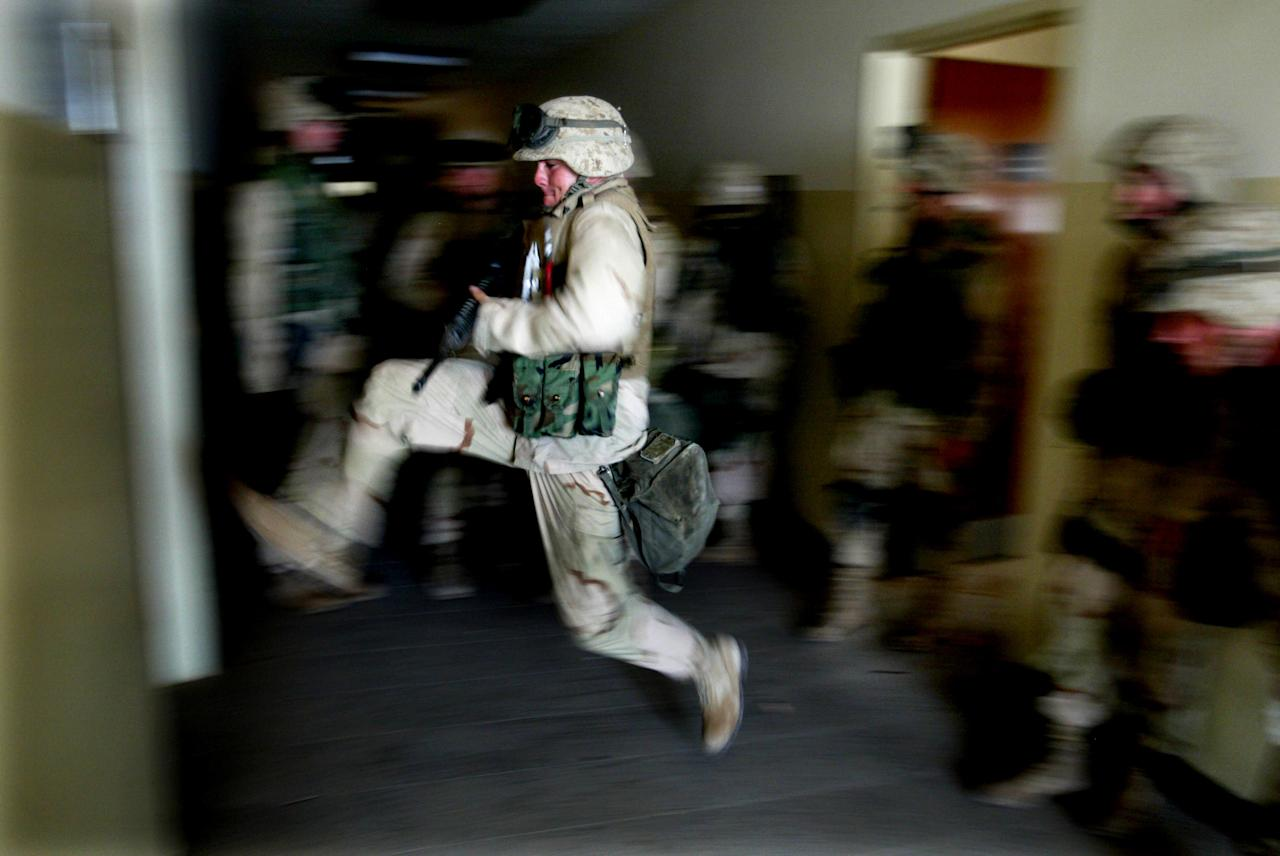 "US Marines kick in a door while securing a building next to the main hospital in central Baghdad April 15, 2003, which will be used as a temporary Iraqi police headquarters. Thousands of guerrillas, including Iraqis loyal to Saddam Hussein and foreign fighters, pose a threat to U.S. troops and complicate efforts to bring stability to postwar Iraq, defense officials said on Tuesday. ""There are still hazards lingering throughout the country of Iraq,"" Brig. Gen. Vincent Brooks told a briefing in Qatar. REUTERS/Jerry Lampen"