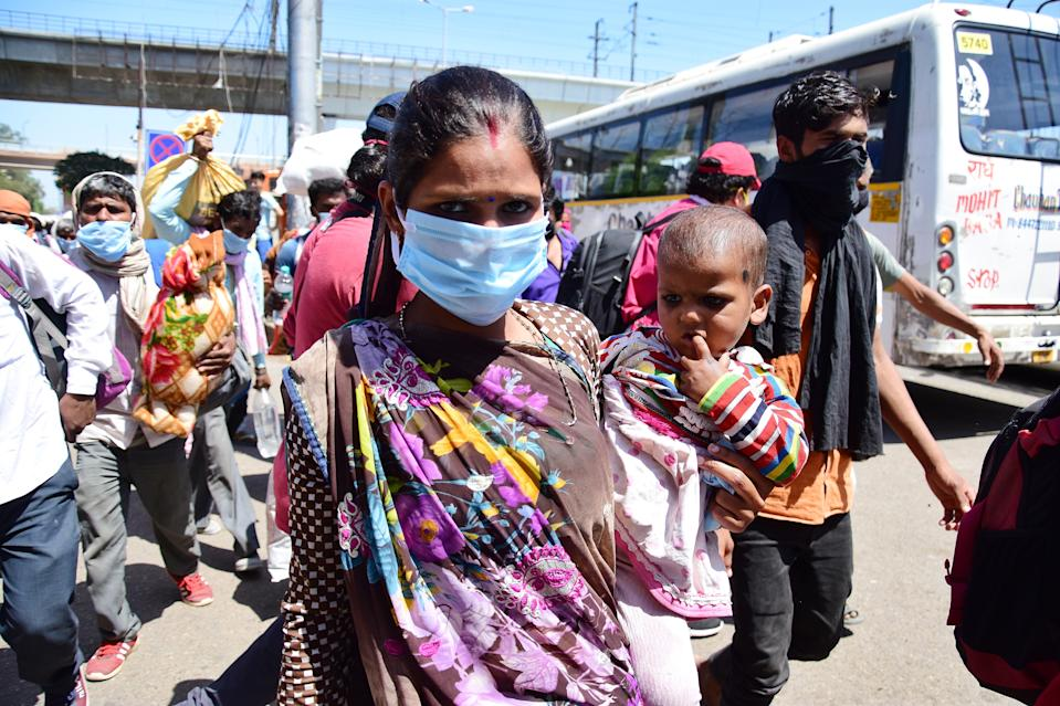 DELHI, INDIA - 2020/03/29: Migrant woman with a baby wearing a face mask as a preventive measure, at Anand vihar bus terminal during the nationwide lock down. The Indian government imposed a 21 day nationwide lock down as a preventive measure against the corona virus pandemic. (Photo by Manish rajput/SOPA Images/LightRocket via Getty Images)