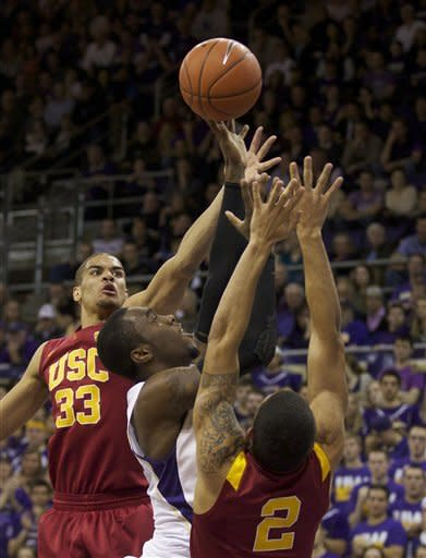 Washington's Tony Wroten, center, drives to the hoop against the USC's Garrett Jackson, left, and Greg Allen during play in an NCAA college basketball game at Alaska Airlines Arena in Seattle Saturday Feb. 4, 2012. (AP Photo/Stephen Brashear)