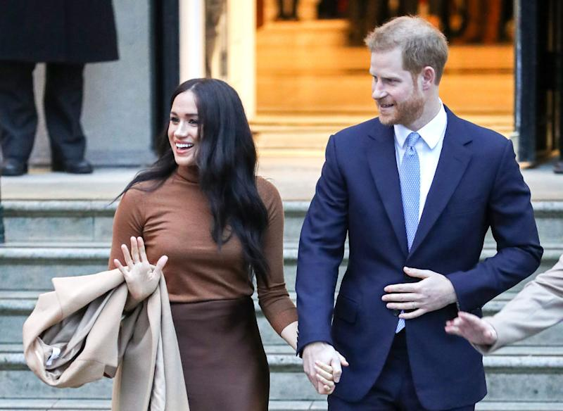 Meghan and Harry hold hands as they wave at the crowd
