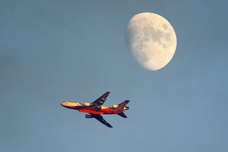 An air tanker battling the Windy Fire flies the moon in the background Thursday, Sept. 16, 2021, on the Tule River Reservation in California. (AP Photo/Noah Berger)