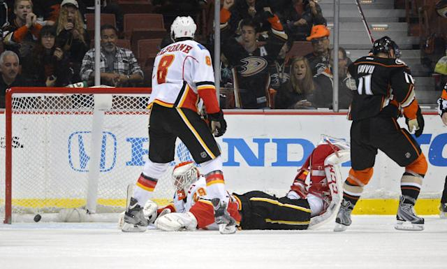 Calgary Flames goalie Reto Berra, center, of Switzerland, can't get to a goal scored by Anaheim Ducks defenseman Sami Vatanen, of Finland, as Ducks center Saku Koivu, right, of Finland, celebrates and center Joe Colborne looks on during the first period of an NHL hockey game, Friday, Nov. 29, 2013, in Anaheim, Calif. (AP Photo/Mark J. Terrill)