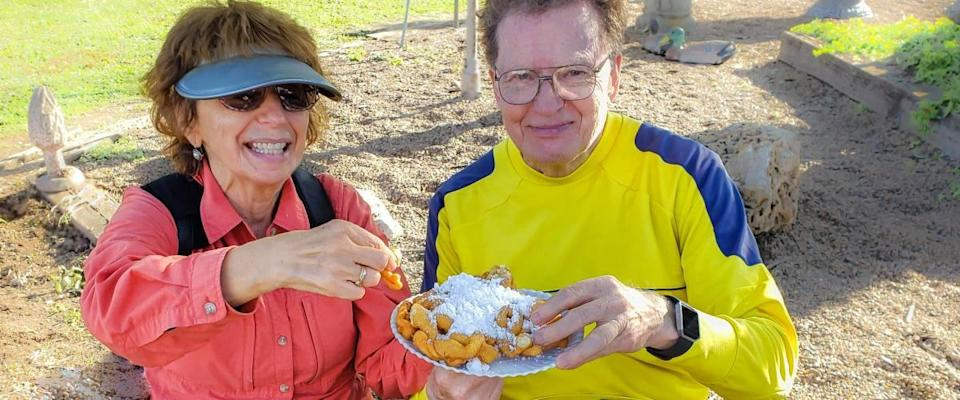 Cheerful senior couple sharing funnel cake with powdered sugar at autumn country fair in Missouri, USA