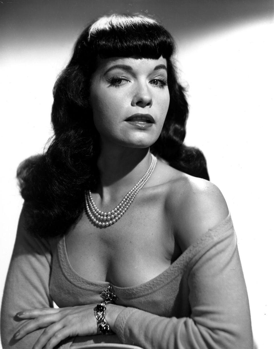 """<p>With her sex appeal, outrageous personality, and iconic style, Bettie Page and <a href=""""http://www.goodhousekeeping.com/beauty/hair/news/g3297/blunt-bangs-trend/"""" rel=""""nofollow noopener"""" target=""""_blank"""" data-ylk=""""slk:her famous bangs"""" class=""""link rapid-noclick-resp"""">her famous bangs</a> influenced those who desired an edgier take on traditional looks.</p>"""