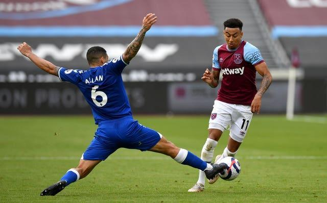 Jesse Lingard, right, is tackled by Everton's Allan