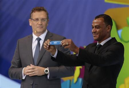"""Former Brazil soccer player Cafu holds the slip showing """"Brazil"""" during the draw for the 2014 World Cup at the Costa do Sauipe resort in Sao Joao da Mata, Bahia state, December 6, 2013. REUTERS/Ricardo Moraes"""