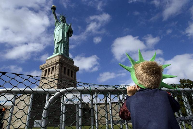 Jackson Blendowski, 6, of New Hampshire, peers up at the Statue of Liberty in New York Harbor, Sunday, Oct. 13, 2013, in New York. The Statue of Liberty reopened to the public after the state of New York agreed to shoulder the costs of running the site during the partial federal government shutdown. (AP Photo/John Minchillo)