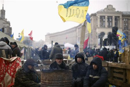 Protesters warm up near a barricade at Independence Square in Kiev
