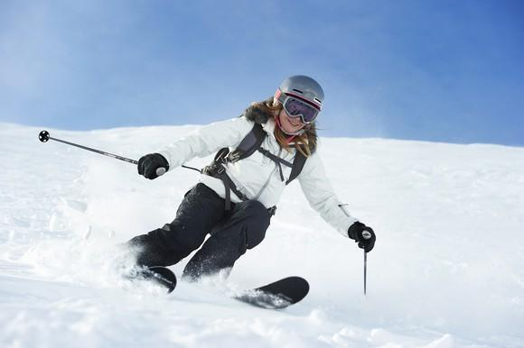 A female skier heads down a hill.