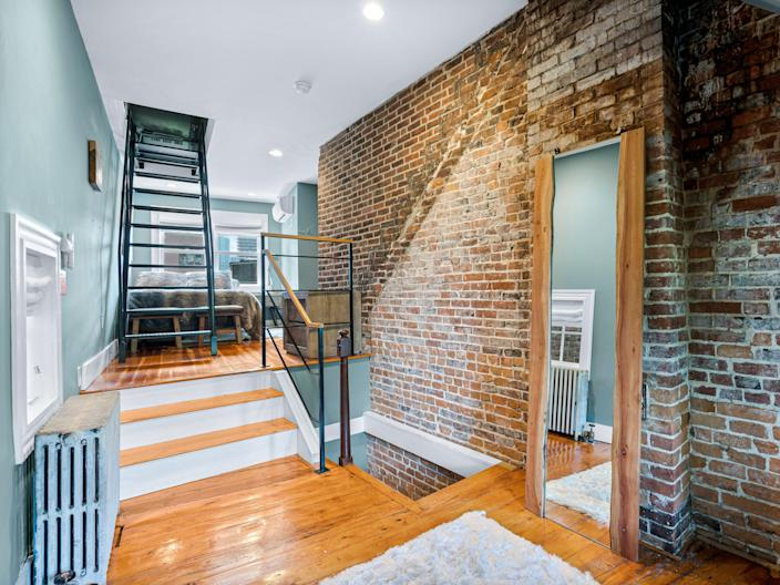 A room with blue walls on the left and exposed brick on the right. Two sets of stairs in the back left corner.