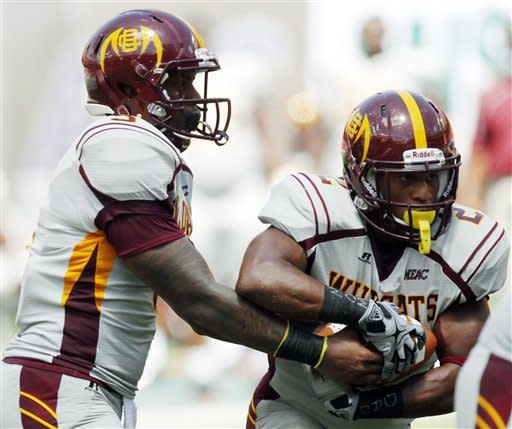 Bethune-Cookman quarterback Jackie Wilson, left, hands off to running back Isidore Jackson in the first half of an NCAA college football game against Miami, Saturday, Sept. 15, 2012, in Miami. (AP Photo/Wilfredo Lee)