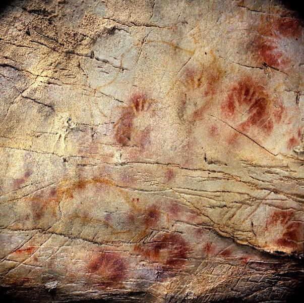 This undated handout photo provided by pedro suara/aaas shows detail of the 'Panel of Hands', El Castillo Cave showing red disks and hand stencils made by blowing or spitting paint onto the wall. A date from a disk shows the painting to be older than 40,800 years making it the oldest known cave art in Europe. The bison overlay the hands and are therefore painted later. New tests show that crude Spanish cave paintings of a red sphere and handprints are the oldest in the world, so ancient they may not have been by modern man. They might have even been made by the much-maligned Neanderthals, some scientists suggest but others disagree. (AP Photo/Pedro Saura, AAAS)