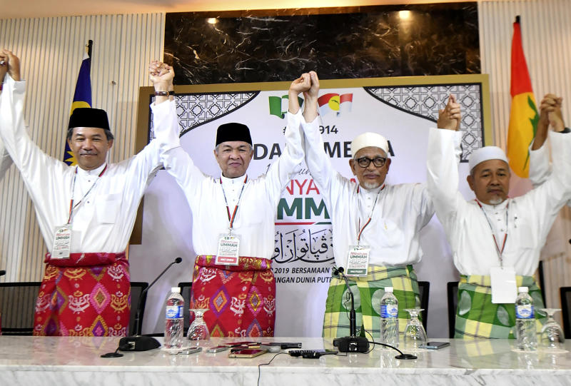 Ahmad Zahid Hamidi, president of UMNO (United Malays National Organisation), center left, and Abdul Hadi Awang, president of PAS (Pan-Malaysian Islamic Party), center right, pose for media after a press conference for an event of officially join alliance in Kuala Lumpur, Malaysia, Saturday, Sept. 14, 2019. Two major opposition parties in Malaysia have forged a political alliance to consolidate support from the country's majority ethnic Malay Muslims, a move that could threaten Prime Minister Mahathir Mohamad's government in the next general elections. (AP Photo)