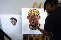 SMU defensive back RaSun Kazadi works on a painting at his apartment Wednesday, Aug. 11, 2021, in Dallas. (AP Photo/LM Otero)