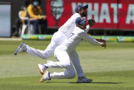 India's Ravindra Jadeja, top, collides with teammate Shubman Gill as he takes a catch to dismiss Australia's Matthew Wade during play on day one of the Boxing Day cricket test between India and Australia at the Melbourne Cricket Ground, Melbourne, Australia, Saturday, Dec. 26, 2020. (AP Photo/Asanka Brendon Ratnayake)