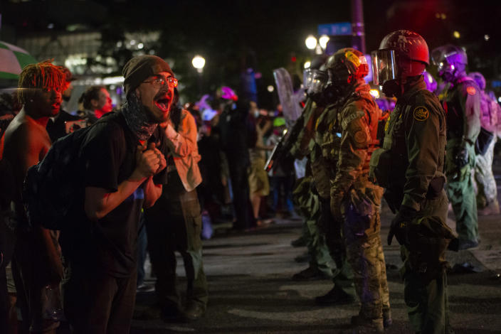 "A protester screams at federal officers after they used tear gas and ""less-lethal"" weapons to disperse a protest on Thursday in Portland, Ore. (Nathan Howard/Getty Images)"
