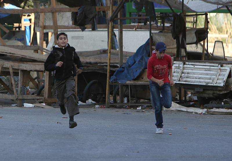 Lebanese citizens run to cross a street to avoid sniper fire, during clashes between supporters and opponents of Syrian President Bashar Assad in the northern port city of Tripoli, Lebanon, Monday, Dec. 2, 2013. Gun battles and rocket fire in the northern Lebanese city of Tripoli killed at least nine people and wounded dozens more over the weekend, the latest clash between supporters and opponents of Syrian President Bashar Assad.(AP Photo/Hussein Malla)