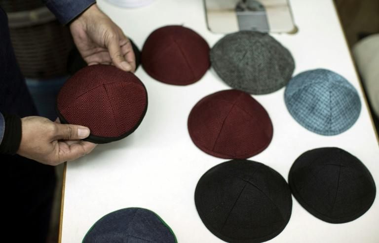 A seamster in Hamas-run Gaza shows off the Jewish skullcaps his factory has produced for export to Israel