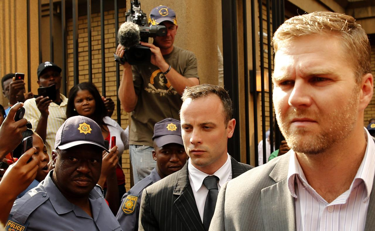 Olympic and Paralympic track star Oscar Pistorius (C) leaves at the end of his trial for the murder of his girlfriend Reeva Steenkamp, at the North Gauteng High Court in Pretoria, March 18, 2014. Pistorius is on trial for murdering his girlfriend Reeva Steenkamp at his suburban Pretoria home on Valentine's Day last year. He says he mistook her for an intruder. REUTERS/Siphiwe Sibeko (SOUTH AFRICA - Tags: CRIME LAW SPORT ATHLETICS)