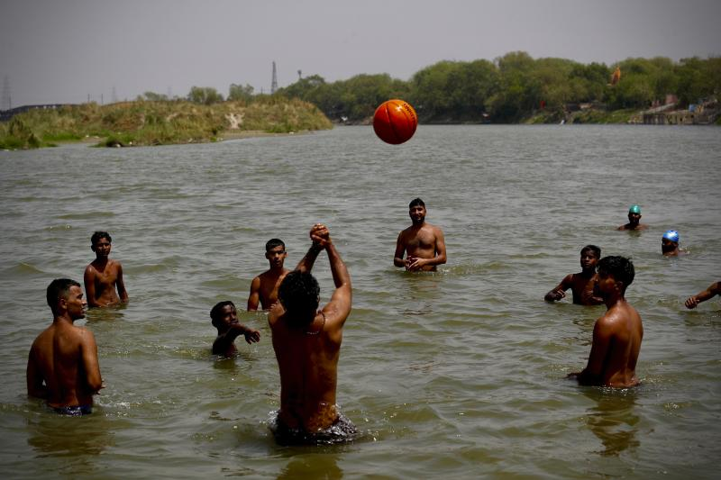 Indian youth cool off in River Yamuna in New Delhi, India, Thursday, May 28, 2020. India grappled with scorching temperatures and the worst locust invasion in decades as authorities prepared for the end of a monthslong lockdown despite recording thousands of new infections every day. (AP Photo/Manish Swarup)