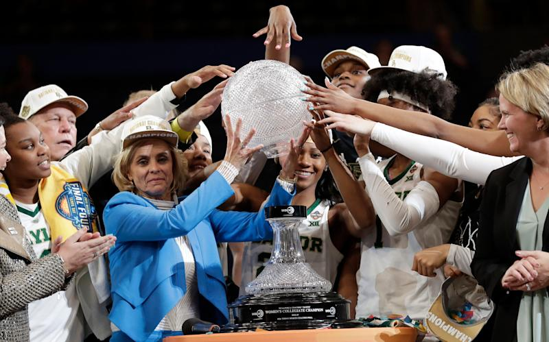Baylor coach Kim Mulkey, in blue, and players raise part of the NCAA/WBCA coaches' trophy after Baylor defeated Notre Dame 82-81 in the Final Four championship game of the NCAA women's college basketball tournament, Sunday, April 7, 2019, in Tampa, Fla. (AP Photo/John Raoux)