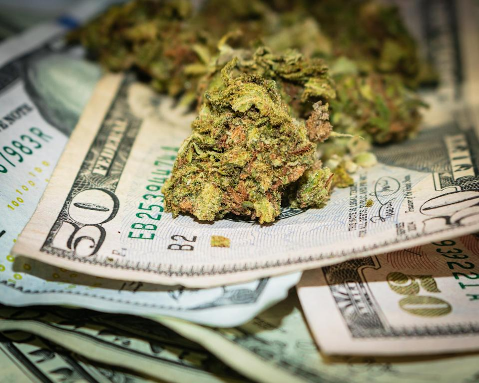 A handful of dried cannabis buds seated atop a messy pile of cash bills.