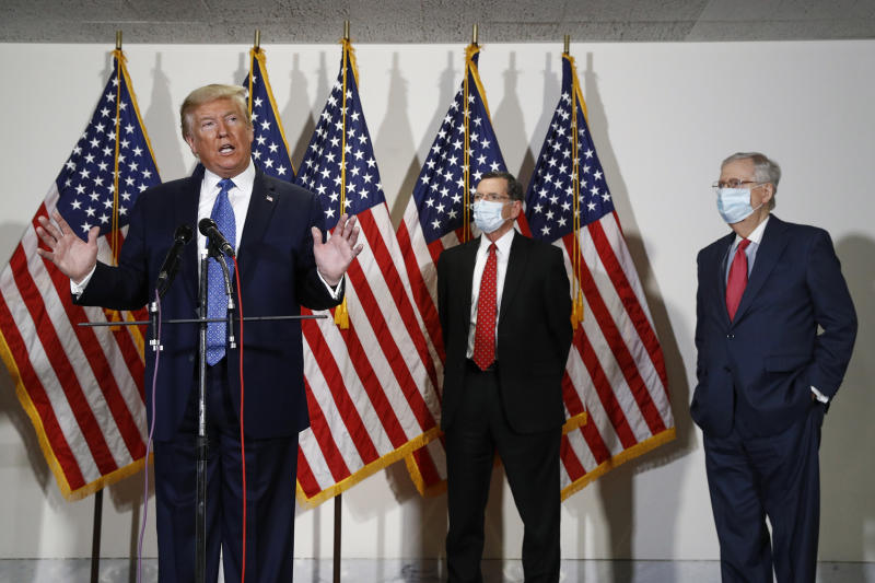 FILE - In this May 19, 2020, file photo President Donald Trump speaks with reporters after meeting with Senate Republicans at their weekly luncheon on Capitol Hill in Washington. Standing behind Trump are Sen. John Barrasso, R-Wyo., second from right, and Senate Majority Leader Mitch McConnell of Ky. GOP candidates are burdened by Trump's lingering unpopularity with suburban voters. They face a potentially crippling fundraising disadvantage against pivotal Democratic incumbents. (AP Photo/Patrick Semansky, File)