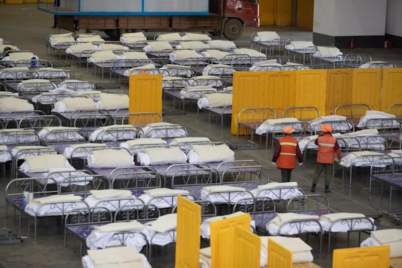 Workers lay beds in the Wuhan living room exhibition center, Wuhan, Hubei Province, China, February 4, 2020.