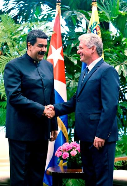 Cuba's newly elected President Miguel Diaz-Canel (R) shakes hands with Venezuela's Nicolas Maduro during a visit to Havana