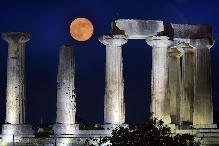 June's full moon, known as the Strawberry Moon, rises above the Apollo Temple in ancient Corinth, on June 17, 2019.