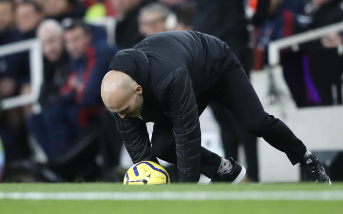 Arsenal's interim head coach Freddie Ljungberg slips as he catches the ball during the English Premier League soccer match between Arsenal and Brighton, at the Emirates Stadium in London, Thursday, Dec. 5, 2019. (AP Photo/Frank Augstein)