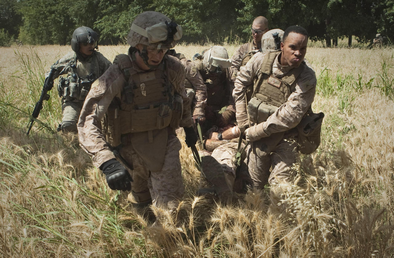 """In this Saturday, June 4, 2011 photo, United States Marines evacuate their wounded comrade Cpl. Burness Britt onto a medevac helicopter from the U.S. Army's Task Force Lift """"Dust Off,"""" Charlie Company 1-214 Aviation Regiment, after he was wounded in an IED strike near Sangin, in the Helmand Province of southern Afghanistan. At the Hunter Holmes Medical Center in Richmond, Va., Britt is facing a long recovery after a large piece of shrapnel cut a major artery on his neck. During his first operation in Afghanistan he suffered a stroke and became partially paralyzed. (AP Photo/Anja Niedringhaus) PART OF A 14-PICTURE PACKAGE BY ANJA NIEDRINGHAUS; ITALY OUT"""