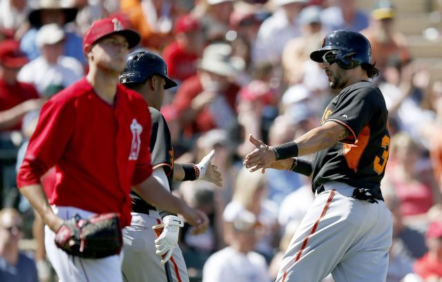 San Francisco Giants' Michael Morse, right, shakes hands with teammate Hector Sanchez after Morse scores a run, while Los Angeles Angels' Tyler Skaggs, left, looks away during the third inning of a spring training baseball game Monday, March 24, 2014, in Tempe, Ariz. (AP Photo/Ross D. Franklin)