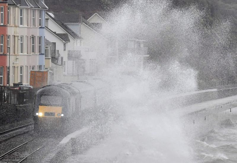 Large waves crash against the seawall during Storm Erik as a train passes through Dawlish in southwest Britain. (REUTERS)