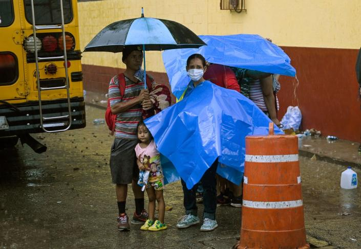 A family stands in the rain under umbrellas and tarps, behind a school bus