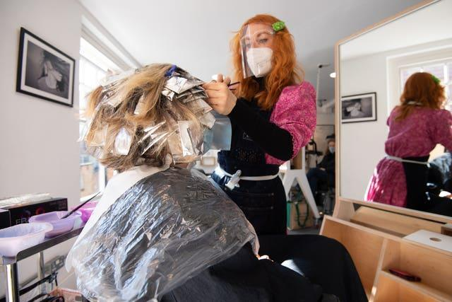 A woman has her hair coloured at the reopening of Flint Hair in Norwich