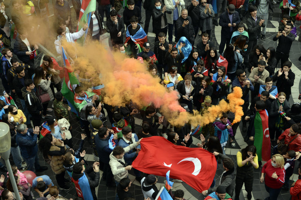 Azerbaijanis celebrate waving national and Turkish flags in Baku, Azerbaijan, Tuesday, Nov. 10, 2020. Armenia and Azerbaijan announced an agreement early Tuesday to halt fighting over the Nagorno-Karabakh region of Azerbaijan under a pact signed with Russia that calls for deployment of nearly 2,000 Russian peacekeepers and territorial concessions. (AP Photo)