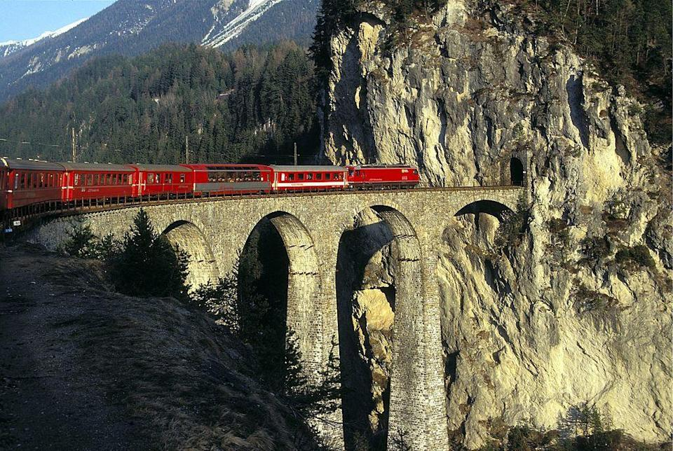 """<p>Get your camera ready. Departing from St. Moritz and ending in Zermatt, <a href=""""https://www.glacierexpress.ch/en/"""" rel=""""nofollow noopener"""" target=""""_blank"""" data-ylk=""""slk:The Glacier Express"""" class=""""link rapid-noclick-resp"""">The Glacier Express</a> takes passengers through the Swiss Alps and every type of landscape, from age-old forests to picturesque towns and, as the name suggests, pristine glaciers. You'll also see popular sites like the Landwasser Viaduct (shown), the Rhine Gorge, otherwise known as the """"Grand Canyon of Switzerland,"""" and the famous Matterhorn. And while the sites alone are enough to entice any traveler to hop aboard, the luxe train offers one of the most opulent classes of train travel. The <a href=""""https://www.housebeautiful.com/lifestyle/a28434452/glacier-express-train-ride-swiss-alps/"""" rel=""""nofollow noopener"""" target=""""_blank"""" data-ylk=""""slk:Excellence Class"""" class=""""link rapid-noclick-resp"""">Excellence Class</a> rivals even the most lavish hotels, offering five course meals, unlimited drinks and coffee, and a bustling bar car for cocktails with a view. </p>"""