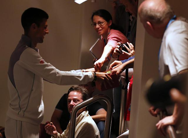 AP reporters Jocelyn Gecker, center, takes a chocolate from Novak Djokovic of Serbia, left, as Djokovic hands out to reporters during a press conference ahead of the Australian Open tennis championship in Melbourne, Australia, Sunday, Jan. 12, 2014. (AP Photo/Shuji Kajiyama)