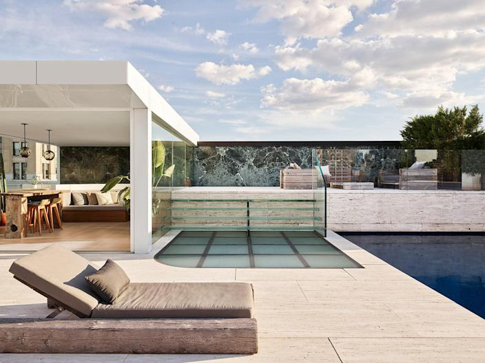 This eight-room duplex penthouse on Park Avenue looks out onto the Chrysler and Empire State Buildings. The apartment features a cantilevered glass-and-wood staircase, a great room with 24-foot-high ceilings, and a master suite with a private library and a dressing room. The highlight of the property is the rooftop pavilion, which showcases a book-matched wall of Green Verde Alpi marble from the same quarry that provided the marble for Mies van der Rohe's Barcelona Pavilion.