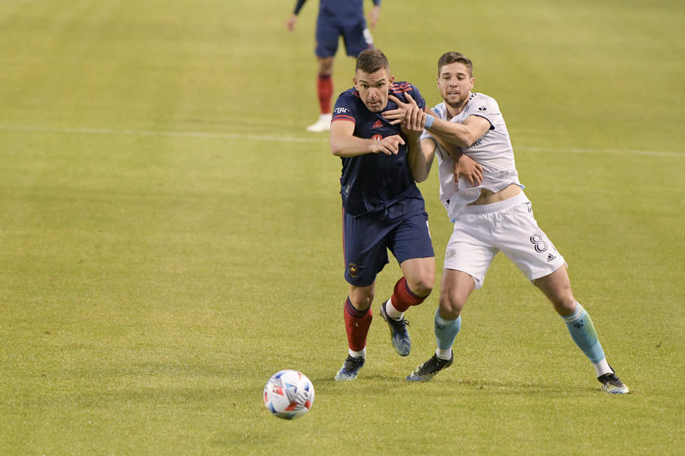 Chicago Fire midfielder Luka Stojanovic (8) and New England Revolution defender Matt Polster (8) battle for control of the ball during the first half of an MLS soccer match in Chicago, Saturday, April 17, 2021. (AP Photo/Mark Black)