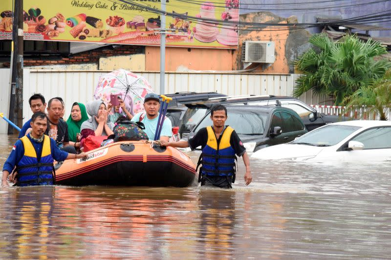 A rescue team evacuates locals on an inflatable boat during a flood after heavy rain in Bekasi, near Jakarta