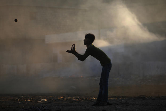 A boy is silhouetted against smoke while playing cricket in a littered ground in a slum area on the outskirts of Karachi October 18, 2011. (REUTERS/Akhtar Soomro)
